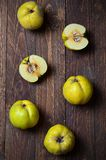 Quince on wooden background. Quince on dark wooden background and beige napkin Royalty Free Stock Images