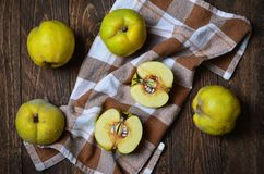Quince on wooden background. Quince on dark wooden background and beige napkin Royalty Free Stock Photos