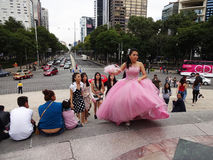 Quinceanera Climbing the Steps. Photo of a quinceanera in a pretty pink dress with her friends on 10/24/15 at the angel of independence in mexico city. The royalty free stock photo