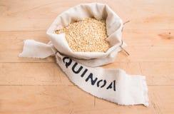 Quinoa νιφάδες σε μια τσάντα υφάσματος κρέμας με την εκτυπωμένη ετικέτα Στοκ φωτογραφία με δικαίωμα ελεύθερης χρήσης