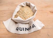 Quinoa νιφάδες σε μια τσάντα υφάσματος με το εκτυπωμένο όνομα Στοκ εικόνα με δικαίωμα ελεύθερης χρήσης