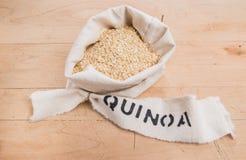 Quinoa οι νιφάδες σε μια τσάντα κύλησαν τη τοπ και εκτυπωμένη ετικέτα Στοκ Εικόνες
