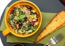 Quinoa σαλάτα των βακκίνιων σπανακιού και φρυγανιά σκόρδου στον πίνακα Στοκ Φωτογραφία