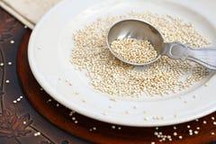 Quinoa. Grain spilled over plate Stock Image