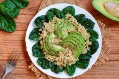 Quinoa, avocat et salade fraîche d'épinards à un plat blanc et à un arrière-plan en bois brun Idée de petit déjeuner d'avocat de  Photos stock