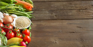 Quinoa in a bowl and fresh vegetables. On a wooden table Stock Images
