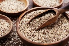 Quinoa in bowl on wooden kitchen table. Healthy and diet superfood product.  stock images
