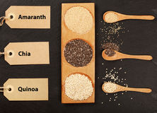 Quinoa, chia and amarantus seeds in wooden spoons with lables. Stock Image
