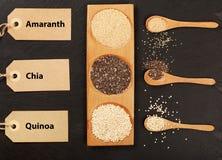 Quinoa-, chia- und amarantussamen in den hölzernen Löffeln mit lables Stockbild