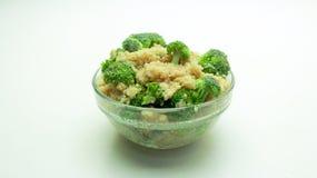 Quinoa com brócolis em uma bacia de vidro em um fundo branco foto de stock