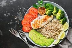 Quinoa com galinha grelhada, abacate, bacia de buddha dos brócolis em um fundo concreto preto Conceito saudável do alimento Vista fotografia de stock royalty free