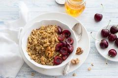 Quinoa con le ciliege, le noci ed il miele freschi sui precedenti blu Fotografie Stock