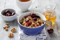 Quinoa con le ciliege, le noci ed il miele freschi sui precedenti di legno Immagine Stock
