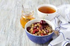 Quinoa con le ciliege, le noci ed il miele freschi sui precedenti di legno Fotografia Stock