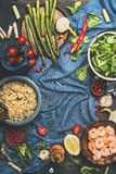 Quinoa cooking. Healthy vegetables and Quinoa . Food background with cooked Quinoa and ingredients for salad on dark blue backgrou Royalty Free Stock Photos