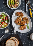 Quinoa crusted chicken, vegetable salad, grilled eggplant and pepper - dinner table. On a dark background royalty free stock photo