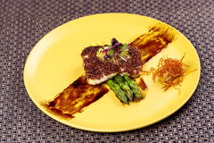 Quinoa crusted fish on asparagus on yellow plate. royalty free stock photos
