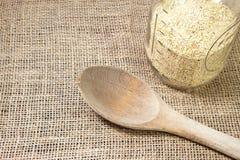 Quinoa e cucchiaio di legno con il fondo-raggiro della tela da imballaggio Fotografie Stock