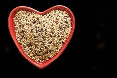 Quinoa in een Rode hart gevormde kom Stock Fotografie