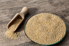 Quinoa in glass dish on wooden background with spice shovel. Royalty Free Stock Photos