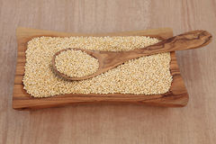 Quinoa Grain. In an olive wood bowl and spoon over papyrus background Stock Photos