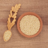Quinoa Grain. In a terracotta bowl and wooden spoon over papyrus background Royalty Free Stock Photos