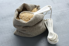 Quinoa grain in small burlap sack and porcelain measuring spoons Royalty Free Stock Images