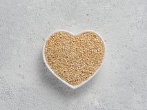 Quinoa in hart-vormige boog op grijze cementachtergrond Royalty-vrije Stock Foto's