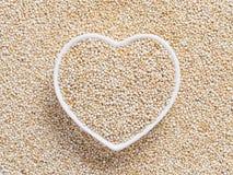 Quinoa in hart-vormige kom op quinoa achtergrond Royalty-vrije Stock Afbeelding