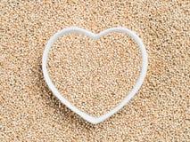 Quinoa in hart-vormige kom op quinoa achtergrond Stock Foto