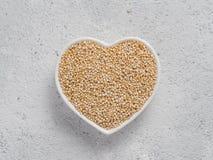 Quinoa in hart-vormige kom op grijze cementachtergrond Royalty-vrije Stock Foto's