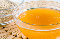 Quinoa and honey in a glass bowl. On straw hot pad. Closeup shot. Healthy food concept Stock Image