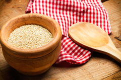 Quinoa i en bunke med en träsked Arkivbild