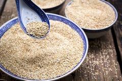 Quinoa in kom met lepel op houten achtergrond stock afbeelding