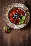 Quinoa malinki na talerzu z czarnym backgro i czarne jagody zdjęcie royalty free