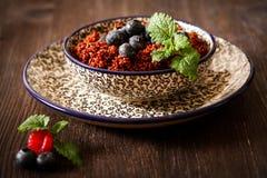 Quinoa malinki na talerzu z czarnym backgro i czarne jagody zdjęcia stock