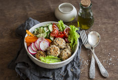 Quinoa meatballs and vegetable salad. Buddha bowl on a wooden table, top view.  Healthy, diet, vegetarian food concept. Stock Photos