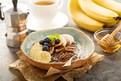 Quinoa porridge with banana, blueberry and pecan nuts stock photos
