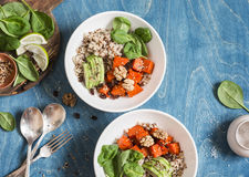Quinoa with pumpkin, spinach and avocado. Healthy quinoa bowl. On a blue background, top view. Stock Photography