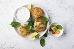 Quinoa ricotta spinach fritters on a white dish with fresh spinach and hot chili peppers. Top View. Quinoa ricotta spinach fritters on a white dish with fresh Stock Photos