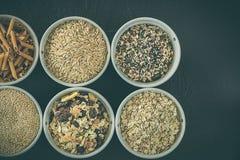 Quinoa, riso sbramato, semi ed avena Intero concetto dell'alimento biologico e del grano per i vegetariani fotografia stock