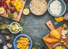 Quinoa sałatkowi składniki: pomidory, avocado, mango, czosnek, feta ser, cytryna, olej Quinoa sałatkowy przygotowanie na ciemnym  obraz stock