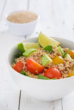 Quinoa salad in bowl with tomatoes and spinach on white wood Stock Photos