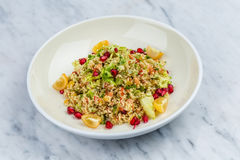 Quinoa salad with pomegranate in white plate. On marbel decks Stock Images