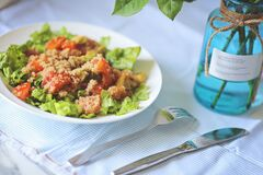 Quinoa salad with salade leaves avokado and tomatoes on a fabric natural color background .Superfoods concept.Serving on table