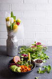 Quinoa salad. Table with fresh clean organic food. Quinoa vegetables salad bowl, salad leaves, flowers bouquet. Superfood or detox eating concept. Spring setting Stock Images