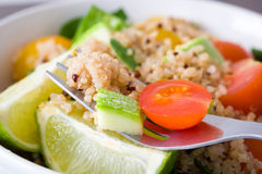 Quinoa salad with tomato and zucchini on a fork Stock Photo