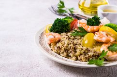 Quinoa salad with vegetables. And shrimp in a dish on the table. Selective focus Stock Image