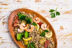 Quinoa salad with vegetables. And shrimp in a dish on the table. Selective focus Royalty Free Stock Image