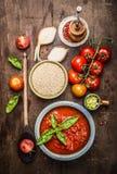 Quinoa sec dans la cuvette en céramique avec la sauce tomate et les ingrédients frais pour faire cuire, vue supérieure Image libre de droits